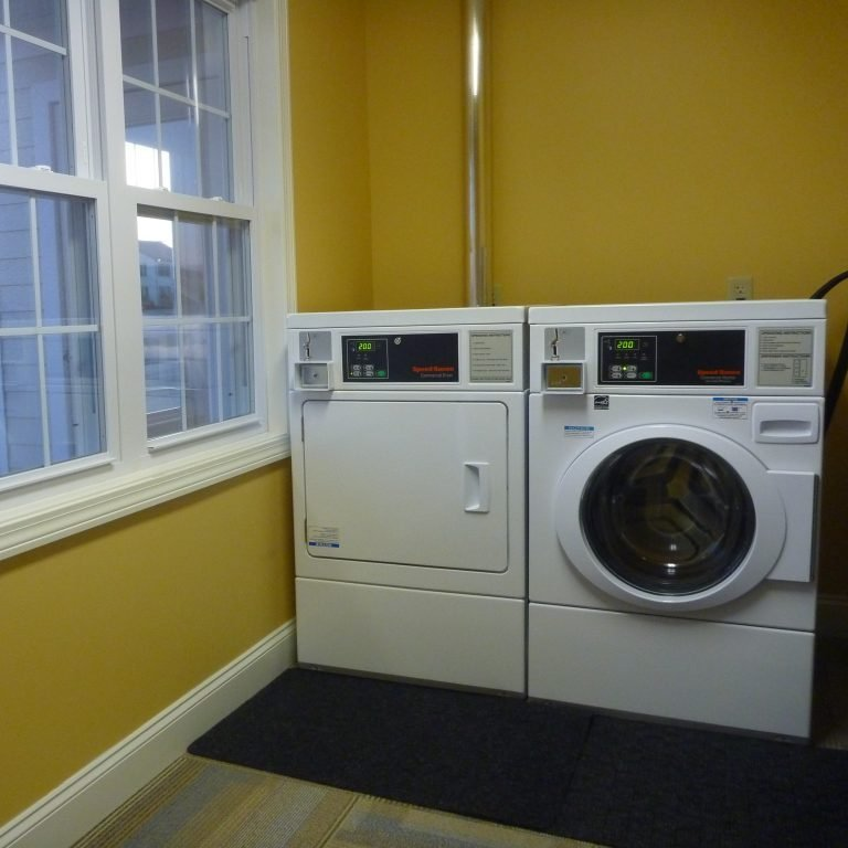 Coin operated washer and dryer next to window in guest laundry room