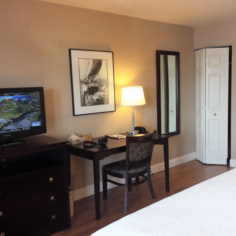 View of guest room with flatscreen TV, writing desk, framed artwork, and folding closet door