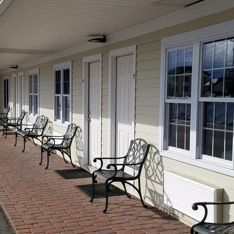 Brick walkway and outdoor seating located in front of guest rooms