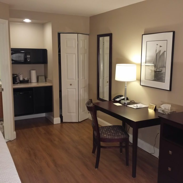 View of guest room with flatscreen TV, writing desk, framed artwork, microwave and mini fridge